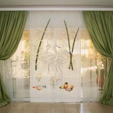 Πράσινη κουρτίνα με σχέδιο κύκνους στο λευκό ύφασμα.
